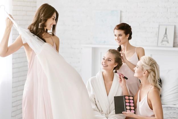 Momenten van voorbereiding. glimlachende opgetogen jonge bruidsmeisjes staan in de witte kamer terwijl ze de bruid helpen zich voor te bereiden en hun vreugde te uiten