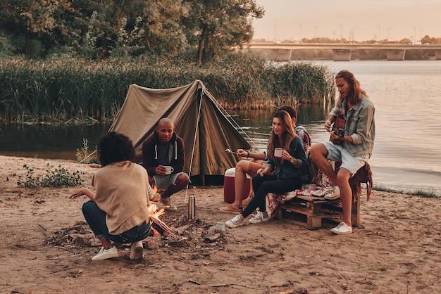 Momenten van vreugde. groep jongeren in vrijetijdskleding die lacht terwijl ze genieten van een strandfeest bij het kampvuur