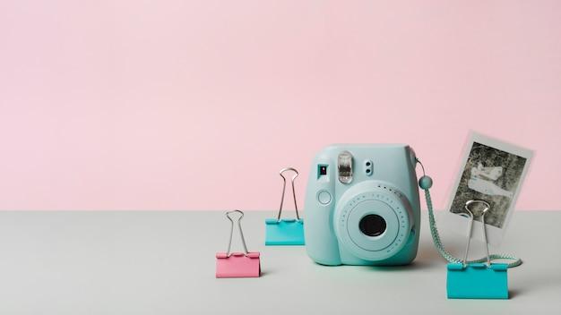 Momentopname foto met mini instant camera en bulldog paperclip tegen roze achtergrond