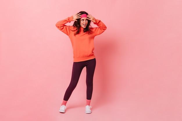 Momentopname in volle groei van jonge donkerharige vrouw in helder sportpak in stijl van de jaren 80