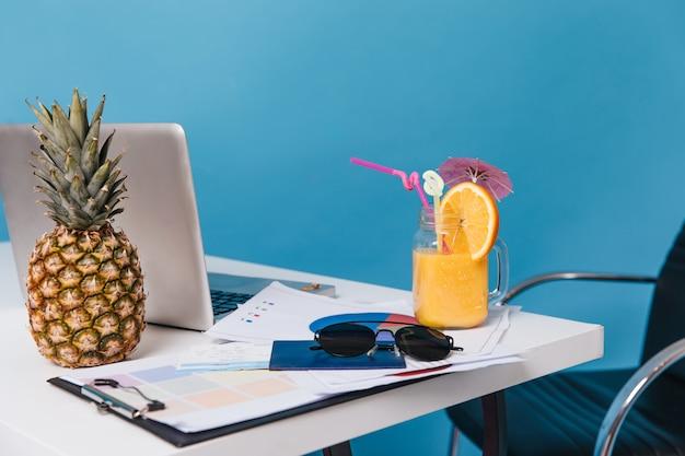 Momentopname van documenten, zonnebril, cocktail, ananas en laptop op tafel op blauwe ruimte.