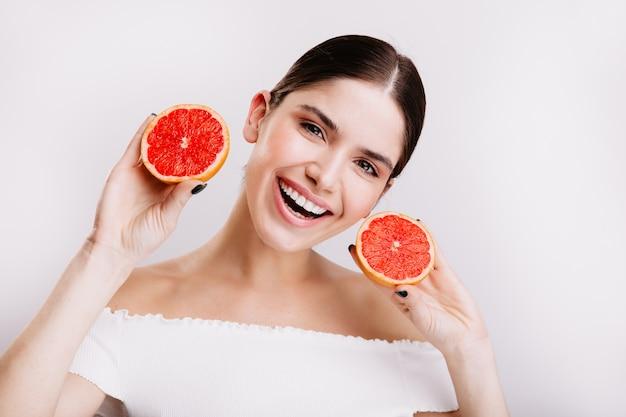 Momentopname van jong meisje met grijze ogen met sneeuwwitte glimlach die sappige en gezonde grapefruits op witte muur tonen.