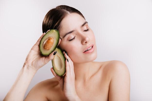Momentopname van meisje zonder make-up op witte muur. dame met gesloten ogen houdt gezonde avocado.
