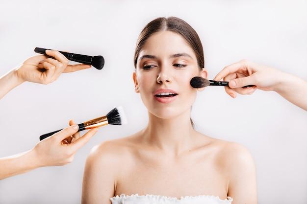 Momentopname van model met een gezonde huid. vele handen met make-upborstels die tot aangezicht van jonge vrouw reiken.