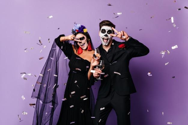 Momentopname van paar met gezichtskunst toont vredesteken. vrouw in zwarte sluier en haar vriendje opknoping met glazen champagne tegen achtergrond van zilveren confetti.