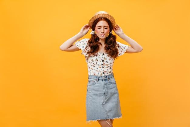 Momentopname van vrouw gekleed in denimrok en witte blouse op oranje achtergrond. vrouw in schipper blaast kauwgom op.