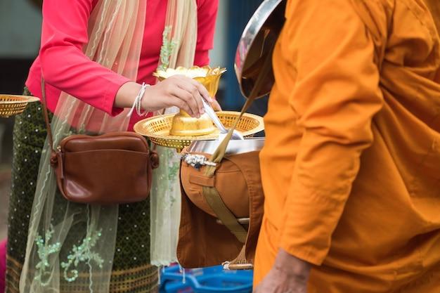 Mon dorp vrouwelijke mensen en bezoekers in traditionele outfit bieden voedsel aan bedelkom van boeddhistische monnik in de vroege ochtend in sangkhlaburi district, kanchanaburi, thailand. beroemde toeristische activiteit.