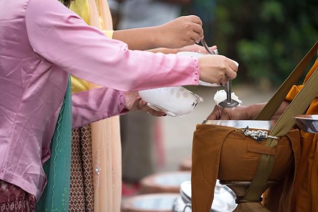 Mon-dorpsmensen en bezoekers in traditionele klederdracht bieden voedsel aan de bedelkom van de boeddhistische monnik in de vroege ochtend in het sangkhlaburi-district, kanchanaburi, thailand. beroemde toeristische activiteit.