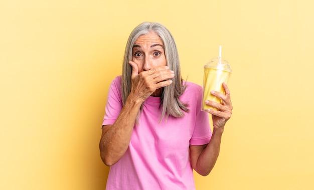 Mond bedekken met handen met een geschokte, verbaasde uitdrukking, een geheim bewaren of oeps zeggen en een milkshake vasthouden Premium Foto