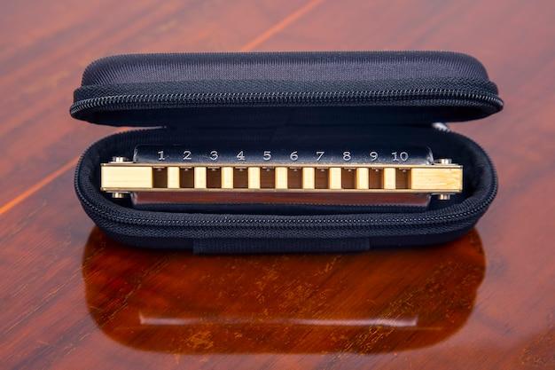 Mondharmonica in een koffer op een houten ondergrond. klassiek muzikaal blaasinstrument.