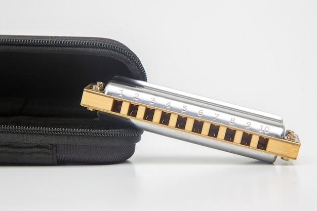Mondharmonica in een koffer op een witte achtergrond. klassiek muzikaal blaasinstrument. Premium Foto