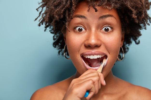 Mondhygiëne en tandheelkunde concept. headshot van verrast jonge afro-amerikaanse vrouw met knapperig haar, tandenborstel en tandpasta gebruikt voor het reinigen van tanden, staart met afgeluisterde ogen geïsoleerd op blauw