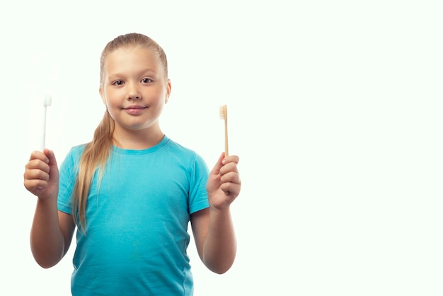 Mondhygiëne. leuk kaukasisch meisje dat bamboe en plastic tandenborstels in haar handen houdt. witte achtergrond, plaats voor tekst. eco producten selectie concept.