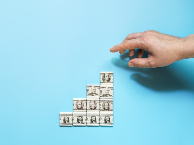 Monetaire winstgroei, inkomsten in concept van stappen van dollartekens en hand die naar doel wijst