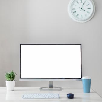 Monitor dichtbij beker, plant en toetsenbord
