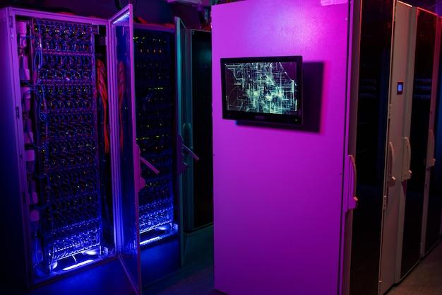 Monitor hangend aan serverrackkast in datacenter in neonpaarse en blauwe kleuren, open kast met blauwe kabels op achtergrond