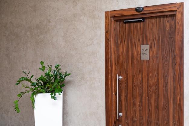 Monitor naast de houten deur in een stijlvol kantoor