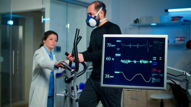 Monitor toont ecg-lezing van man-atleet die op crosstrainer rent en bespreekt met medisch onderzoeker