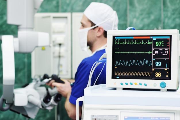 Monitor vitale functie, chirurg en de microscoop. moderne neurochirurgie