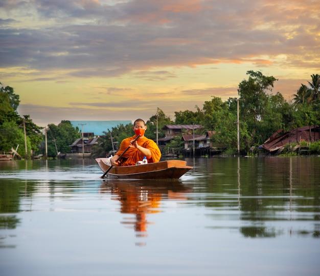 Monnik aalmoes om boot die op water in de ochtendzonstijging roeien