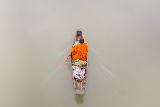Monnik in rijenboot die voedselaanbod van mensen langs kanaal ontvangt.