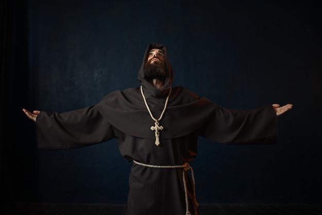 Monnik in zwart gewaad met kap geknield en biddend