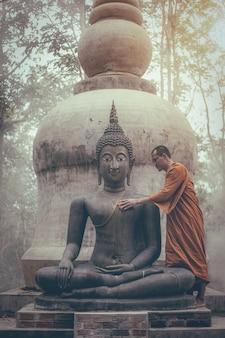 Monnik schrobben boeddhabeeld bij tempel