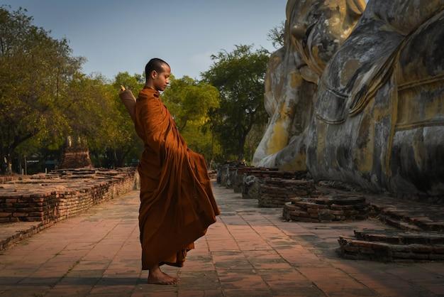 Monnik staat bij de phra non-tempel, de lokayasutharam-tempel, het district phra nakhon si ayutthaya