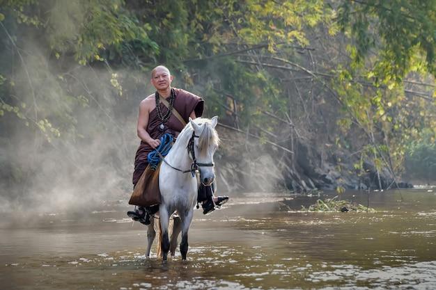 Monniken reden paarden over de rivier voor aalmoezen.