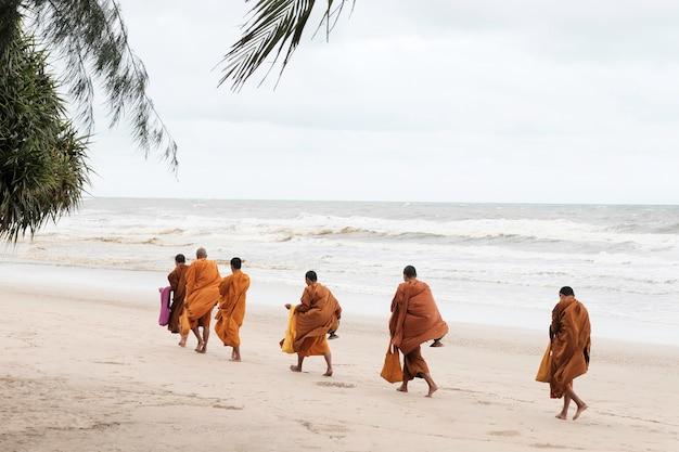 Monniken wandelen langs het strand