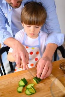 Mono-ouderlijke vader en kind snijden komkommer