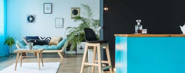 Monochromatische groenblauwe woonkamer met een kitchenette en een stijlvolle barkruk