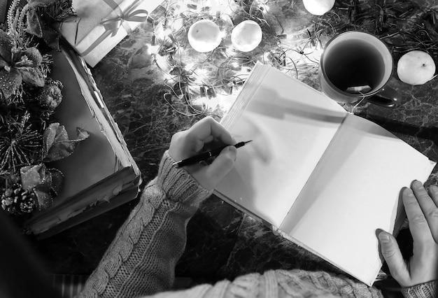 Monochrome foto van een man met een blanco boek in zijn handen voor de nieuwjaarstafel met versieringen