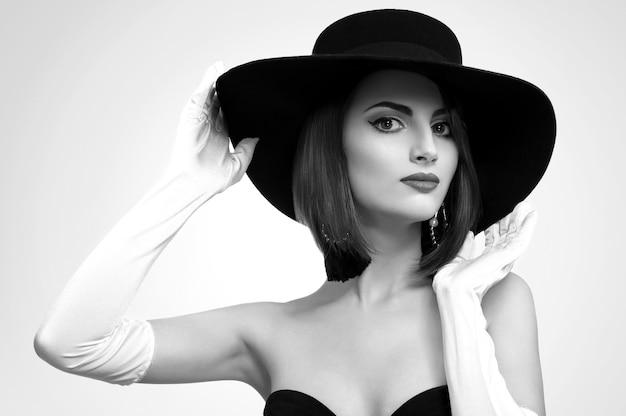 Monochrome schoonheidsshots van een elegante vrouw met een hoed