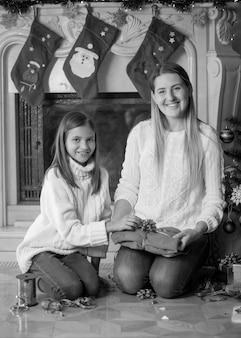 Monochroom beeld van gelukkige jonge moeder en dochter die kerstcadeautjes inpakken op de vloer in de woonkamer