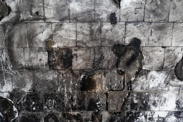 Monochroom gevlekte betegelde muur na brand