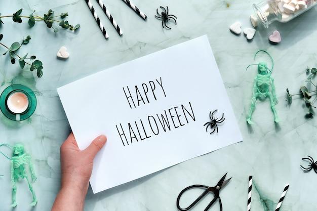 Monochroom halloween plat leggen met skelet in de hand, eucalyptus, theelichtje, schaar, wiebelogen, drinkrietjes en harten.
