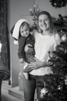 Monochroom portret van gelukkige moeder en babyjongen die kerstboom versieren