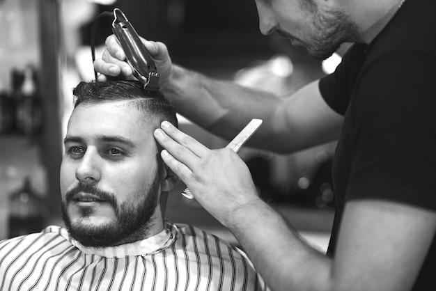 Monochroom van een jonge, bebaarde man die zijn haar laat stylen door een professionele kapper