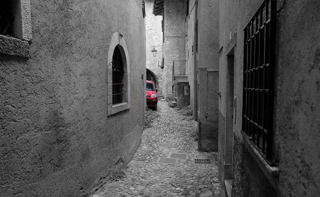 Monocolor rode auto in zwart-wit straat