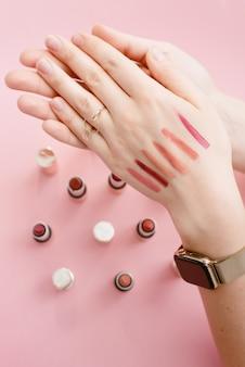 Monster lippenstift op de dunne hand van een meisje. stalen van verschillende lippenstiften.