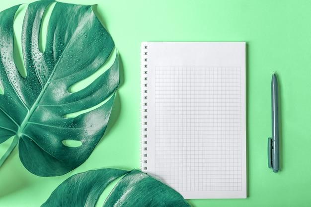 Monstera bladeren, een geruit notitieboekje en een pen op een lichtgroene achtergrond. ruimte kopiëren. detailopname