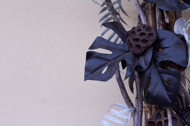 Monstera zwart blad en tropisch decor tegen een lichte muur, trendy interieurdetails