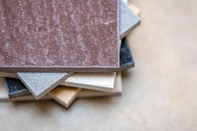Monsters van natuursteen voor keukenwerkbladen en vloertegels. steenmonsters voor werkbladen op grijze achtergrond, kopieer ruimte voor ontwerp of tekst.