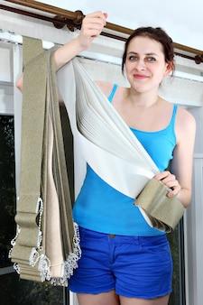 Montage en installatie van verticale, stoffen, jaloezieën. meisje met stroken doek stof verticale blinde latten