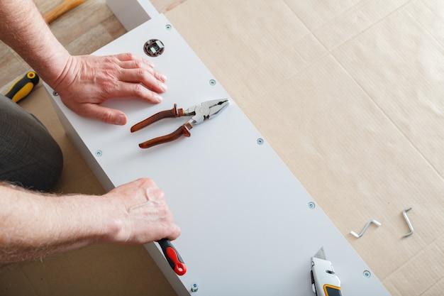 Montage van meubels. mannelijke handen meester verzamelt meubels met behulp van schroevendraaier tools, instrument thuis. verhuizen, woningverbetering, meubelreparatie en renovatie. ruimte kopiëren.