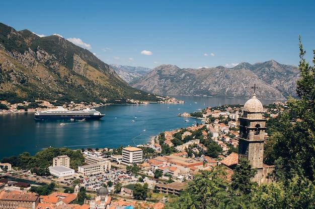 Montenegro adriatische zee en bergen. schilderachtig panorama van de stad kotor op een zomerse dag. panoramisch uitzicht over de baai van kotor en de stad. cruiseschip in de baai van kotor