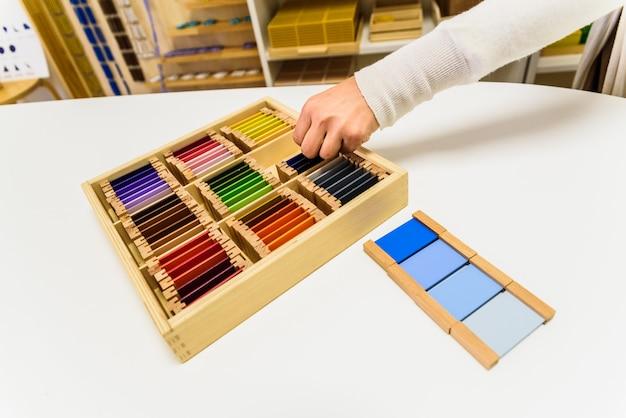 Montessori-studentenhanden die sensorisch materiaal op een school gebruiken.