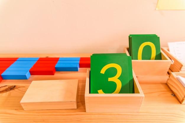 Montessorisch numeriek materiaal opgeslagen op de planken van een school