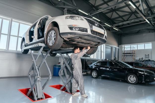Monteur auto op lift in mechanische winkel of garage, interieur van auto reparatie werkplaats repareren